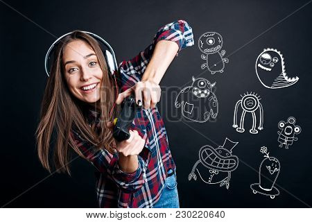 Exciting Game. Excited Pretty Young Woman Leaning To The Right While Holding A Modern Game Console A