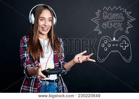 Game Over. Emotional Young Beautiful Woman Wearing Big Headphones And Looking Surprised While Holdin