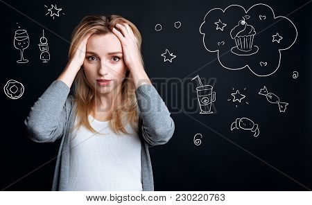 Diet. Hungry Young Woman Touching Her Head And Feeling Worried While Being On A Diet And Dreaming Ab