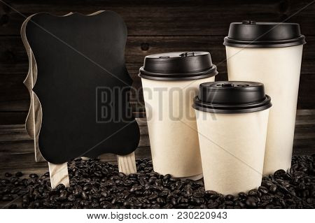 Cups Of Coffee And Coffee Beans On An Old Wooden Table. Wooden Wall In Background.