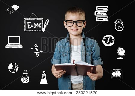 Clever Pupil. Calm Clever Enthusiastic Pupil Wearing Big Glasses And Smiling Cheerfully While Holdin