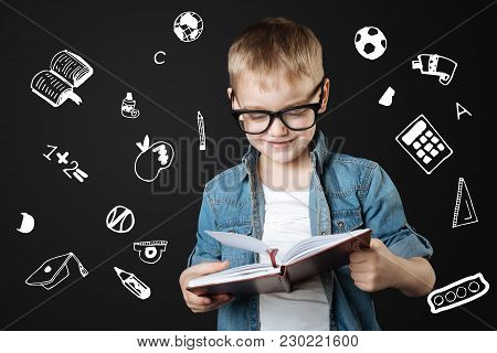 Diligent Schoolboy. Cute Little Clever Boy Looking Interested While Reading Important Information In
