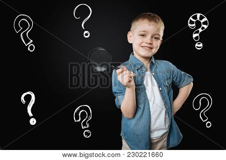 Little Scientist. Enthusiastic Little Curious Boy Standing With A Big Magnifying Glass In His Hand A