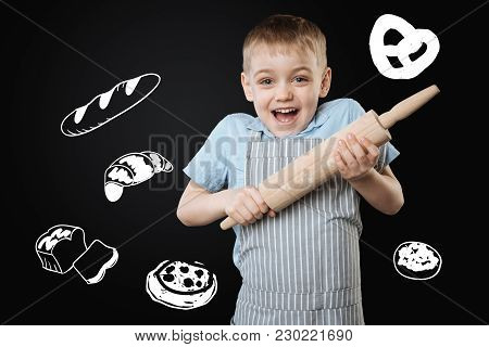 Lets Cook. Adorable Enthusiastic Little Boy Feeling Excited While Holding A Big Wooden Rolling Pin A