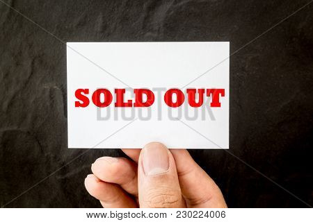 Hands Holding Blank Business Card With Text Sold Out On Black Background