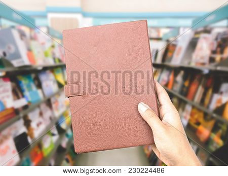 Hands Holding A Book On Bookshelf In Library Blur Background