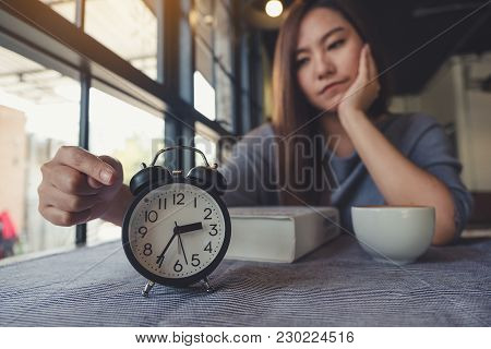 An Asian Woman Pointing At A Black Clock With Feeling Bored While Waiting For Someone