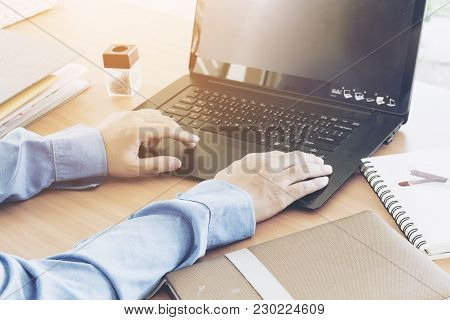 Businessman Using Laptop On A Wooden Table