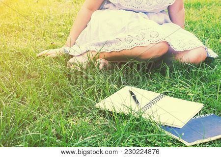 Woman Reading A Book On Green Grass