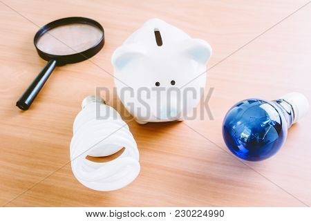 Energy Saving Lamp With Piggy Bank On Wooden Table
