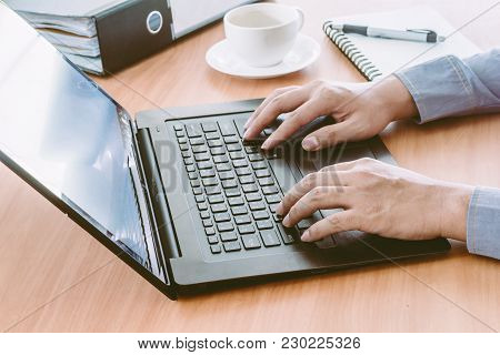 Businessman Using Laptop With Coffee On Table