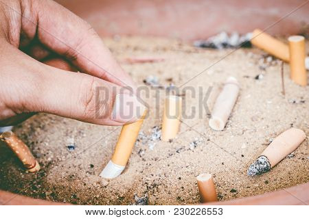 Male Hand Stubbing Out Cigarette In Sand Ashtray Bin