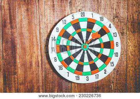 The Darts Dartboard On A Wooden Background