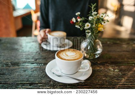 Two Cups Of Coffee And A Vase Of Flowers On A Wooden Table, The Girl Holds In Her Hand One Cup Of Co