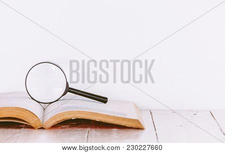 Magnifying Glass And Books On Wooden Table