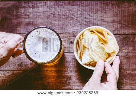 Hand Holding Beer In Glass With Snack Potato Chips On Wooden Table