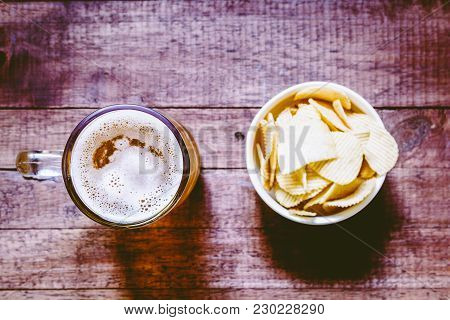 Beer In Glass With Snack Potato Chips On Wooden Table