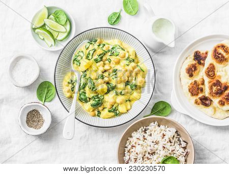 Vegetarian Chickpea, Spinach, Potato Curry, Naan Flatbread And Wild Rice On White Background, Top Vi