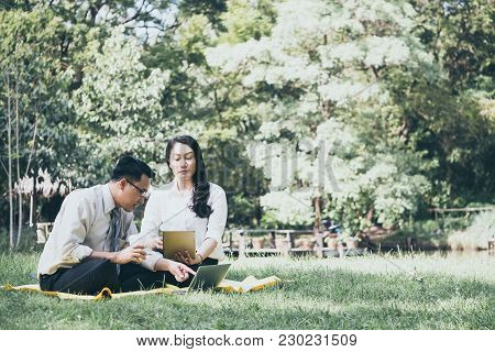 Happy Asian Business People Are Dicussing, Working And Relaxing While Sitting In The Park.