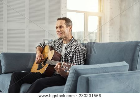 Favourite Activity. Good-looking Exuberant Well-built Man Smiling And Playing The Guitar While Sitti