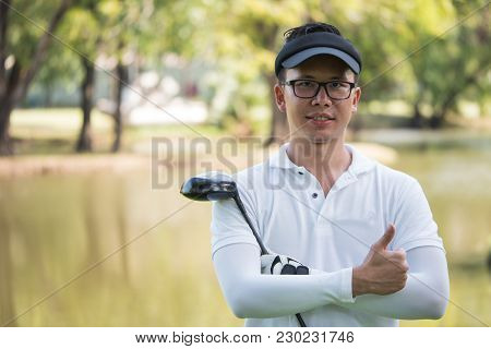 Portrait Of Asian Young Male Golfer With Golf Club On The Golf Course.
