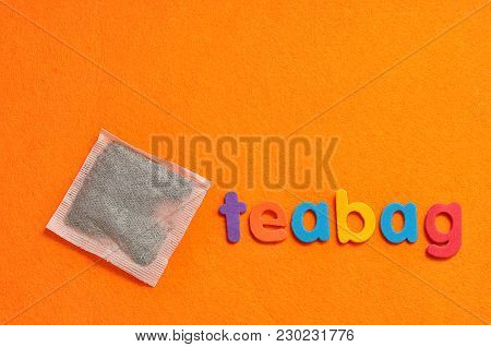 A Teabag With The Word Teabag On An Orange Background