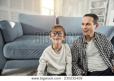 Kidding. Attractive Exuberant Fair-haired Boy Smiling And Wearing Big Glasses And His Father Laughin