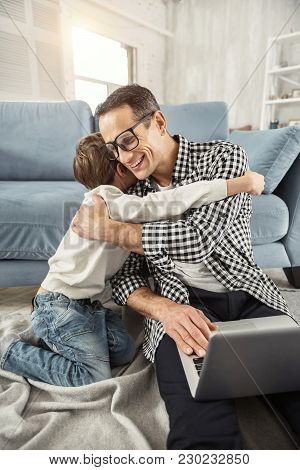 I cherish you. Handsome exuberant dark-haired father sitting on the floor and working on his laptop and his son hugging him poster