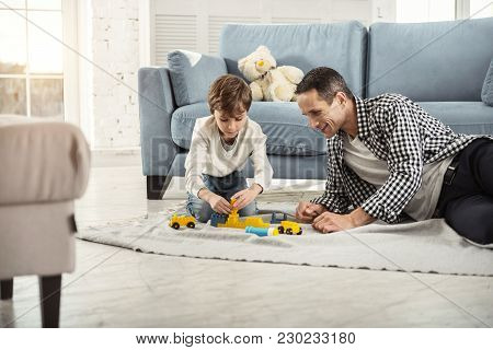 Time For Playing. Handsome Concentrated Fair-haired Boy Playing With His Erector Set And His Daddy S