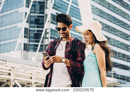 Couple Asian Travelers Are Walking On City Street And Looking At Interesting Places To Travel From S