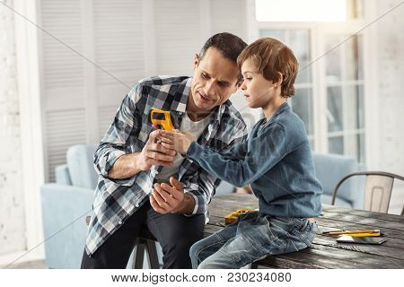 My Son. Handsome Serious Dark-haired Man Showing Instruments To His Son While Sitting On The Table A