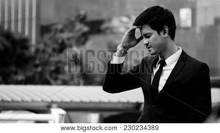 Frustrated Asian Young Business Man Standing In Front Of The Office Building. Black And White Tone.