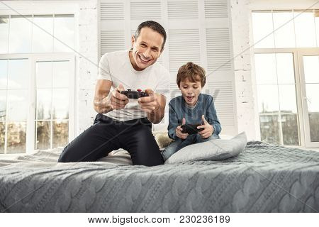 Relaxing At Home. Good-looking Content Well-built Father Smiling And Playing Games With His Son And