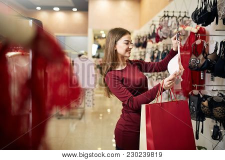Young Woman Chooses Sexy Brassiere Among Set In A Boutique. Pretty Girl Considers Bra With Shopping
