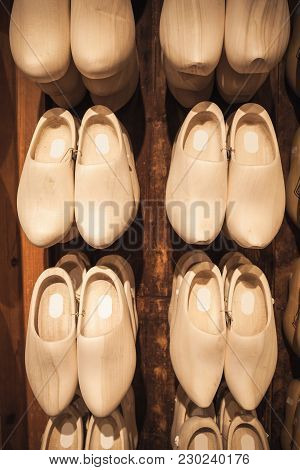 Uncolored New Clogs Made Of Poplar Wood Hanging In Souvenir Shop. Klompen Are Traditional Dutch Shoe