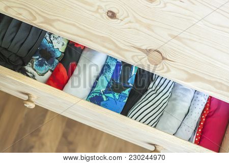 Open light wooden dresser drawer with colorful clothes. poster