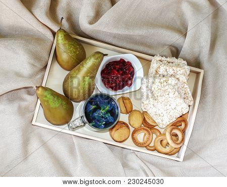 Breakfast In Bed In A Wooden Tray With Pears, Pear Jam, Bisquits, Sweet Cookies, Teapot And Cup Of O