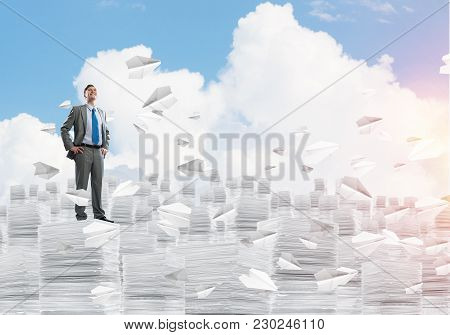 Confident Businessman In Suit Standing Among Flying Paper Planes And Looking Away With Cloudly Skysc