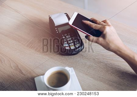 Woman Paying With Mobile Phone For Coffee In Cafe. Mobile Phone Payment