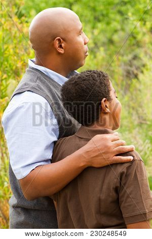 Rear View Of A Father Comforting His Son.