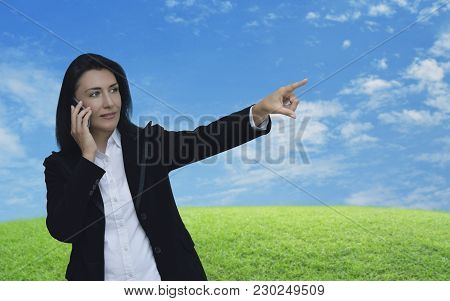 Caucasian Business Woman Talking On Her Cell Phone And Pointing Or Touching Touchscreen Over Green G