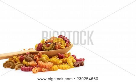 Background Of Raw Colored Macaroni In The Wooden Spoon. Isolated On White Background. Copy Space, Te
