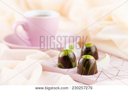 Luxury Bonbons With Cup Of Coffee On Pastel Pink Background. Exclusive Handmade Chocolate Candy Pain