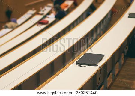 Black Notebook Laptop Computer On The Desk In University Auditorium