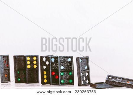 Black Domino On A White Wooden Table