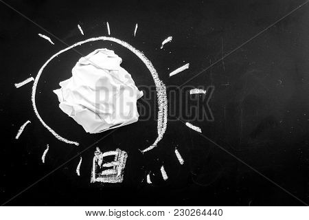 Hand Drawn Light Bulb With Crumpled Paper Ball On Blackboard