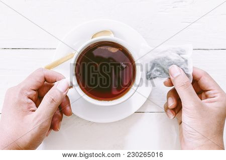 Hand Holding Cup Of Tea With Tea Bag On Wooden Table