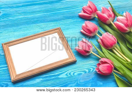 Tulip Flowers And Empty Photo Frame Of A Loved One Copy Space On Blue Wooden Table Board Background.