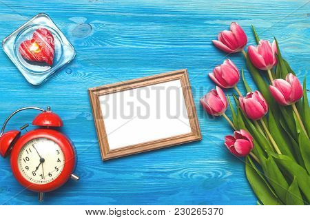 Tulip Flowers And Empty Photo Frame Of A Loved One Copy Space, Alarm Clock And Burning Candle On Blu
