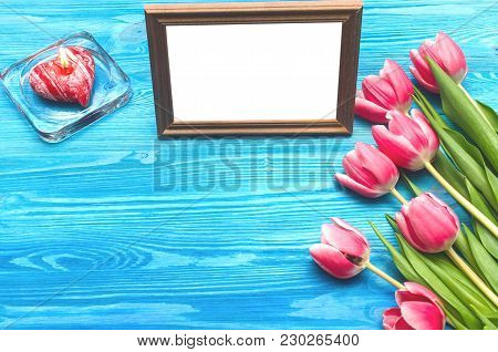 Tulip Flowers And Empty Photo Frame Of A Loved One Copy Space And Burning Candle On Blue Wooden Tabl